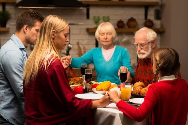 Famiglia che prega a tavola e tenendosi per mano Foto Gratuite