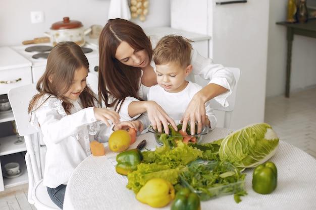 Famiglia che prepara un'insalata in una cucina Foto Gratuite