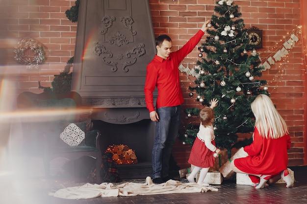 Famiglia che si siede a casa vicino all'albero di natale Foto Gratuite