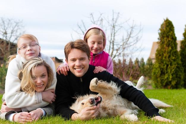 Famiglia che si siede insieme con i cani su un prato Foto Premium
