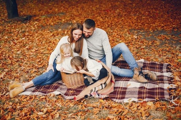 Famiglia con bambini carini in un parco in autunno Foto Gratuite