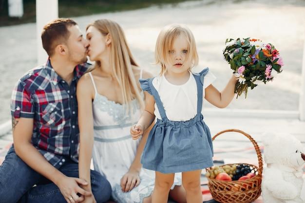 Famiglia con la figlia che gioca su una sabbia Foto Gratuite