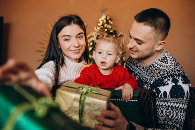 Famiglia con la piccola figlia che si siede dall'albero di natale e che disimballa il contenitore di regalo Foto Gratuite