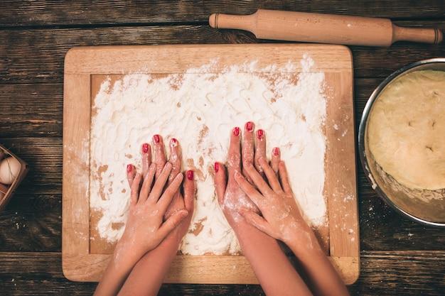 Famiglia cucina torte fatte in casa, le mani della mamma e della figlia nella farina su un tavolo. Foto Premium