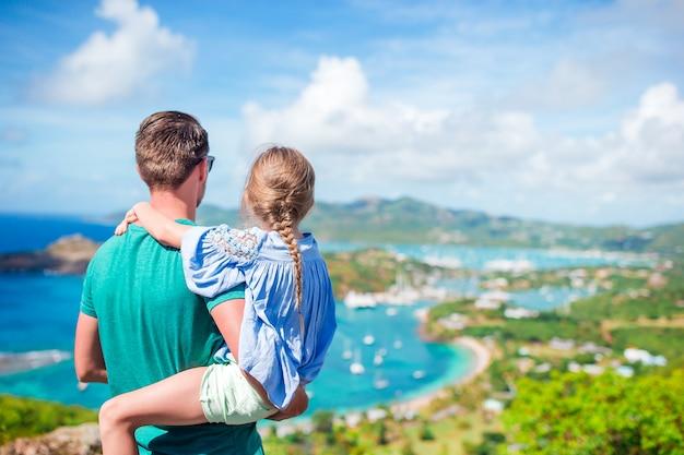 Famiglia del papà e del bambino che godono della vista del porto inglese pittoresco all'antigua in mar dei caraibi Foto Premium