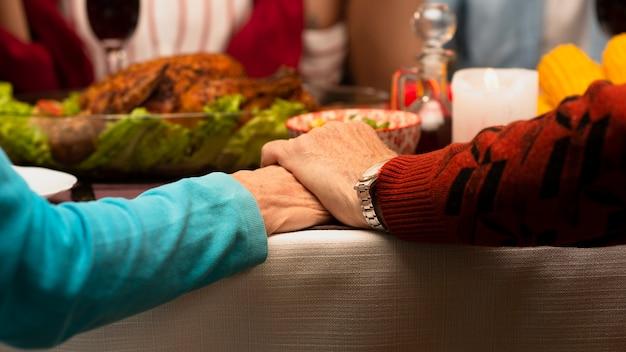 Famiglia del primo piano che si tiene per mano sull'evento di ringraziamento Foto Gratuite
