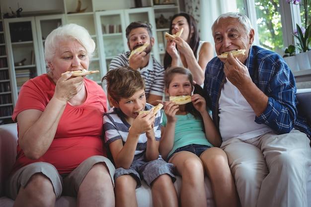 Famiglia di diverse generazioni che mangia pizza insieme Foto Premium