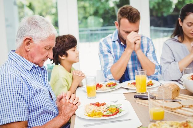 Famiglia di diverse generazioni che prega al tavolo da pranzo Foto Premium