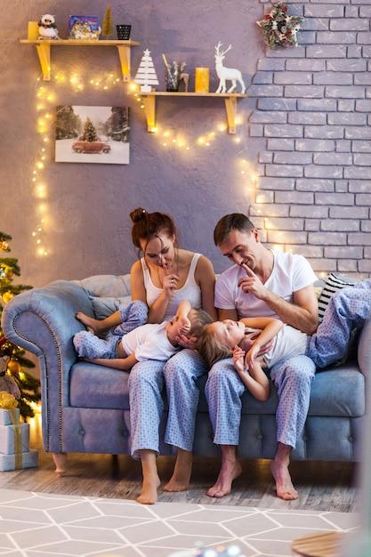 Famiglia di natale con due bambini nel bellissimo soggiorno Foto Premium