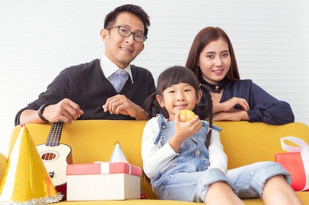 Famiglia di natale e goditi le vacanze. il bambino mangia la mela. la madre e il padre sorprendono il regalo attuale con i bambini al salone bianco. Foto Premium