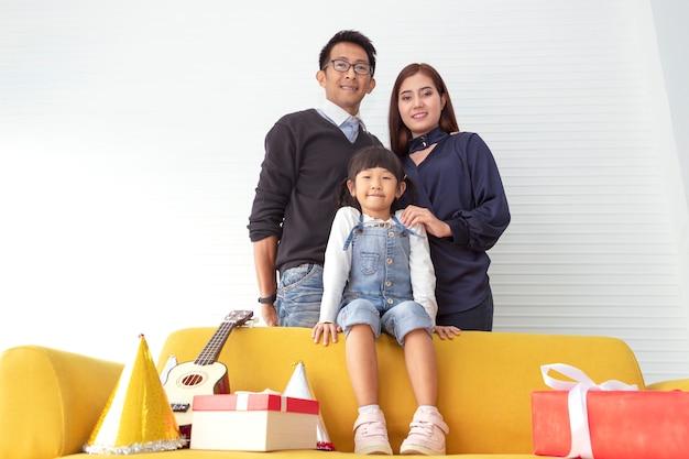 Famiglia di natale e vacanze allegre. la madre, il padre ed i bambini si avvicinano al regalo attuale al salone bianco. Foto Premium