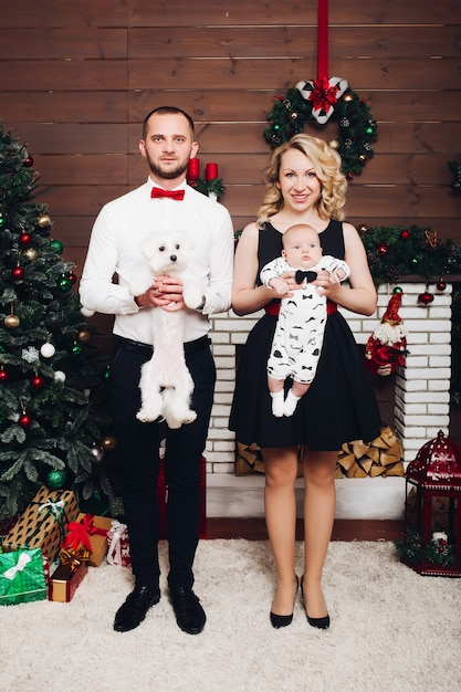 Famiglia divertente che sta vicino al cane e al figlio della tenuta del camino in mani e nel sorridere Foto Premium