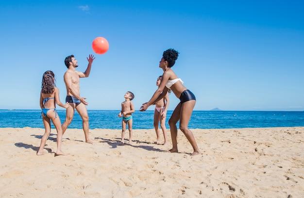 Famiglia divertente con una palla Foto Gratuite