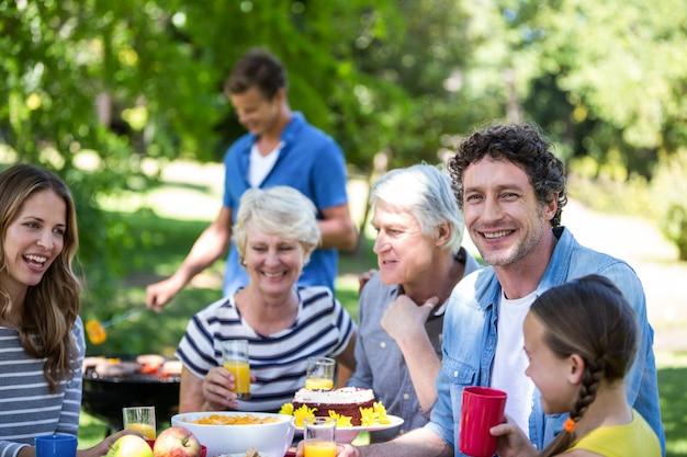 Famiglia e amici che hanno un picnic con barbecue Foto Premium