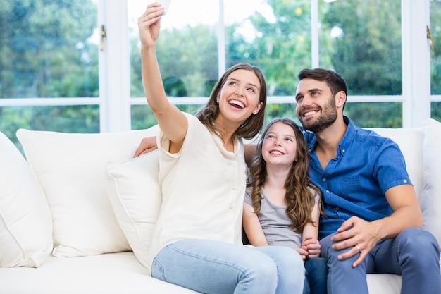 Famiglia facendo clic sui selfie mentre era seduto sul divano Foto Premium