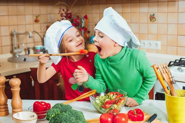 Famiglia felice bambini divertenti stanno preparando un'insalata di verdure fresche in cucina Foto Gratuite