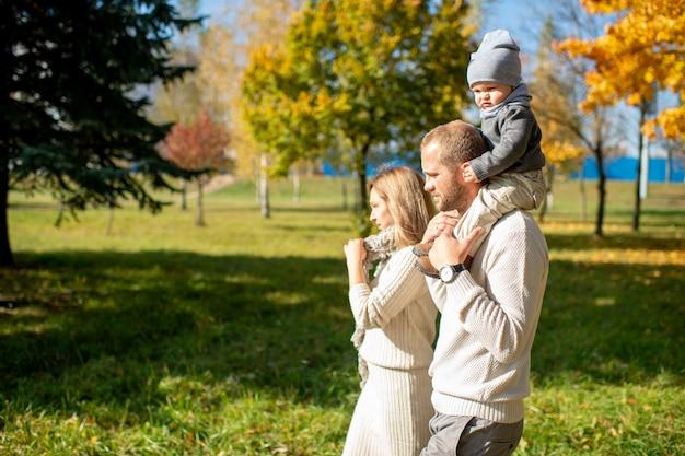 Famiglia felice che cammina con il loro bambino sulle spalle nel parco soleggiato. Foto Premium