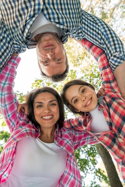 Famiglia felice che forma calca in parco contro il cielo Foto Gratuite