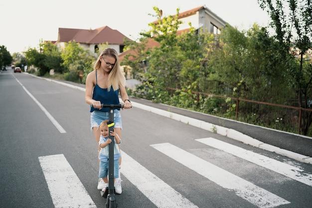 Famiglia felice che guida scooter nel quartiere sulla strada. Foto Gratuite