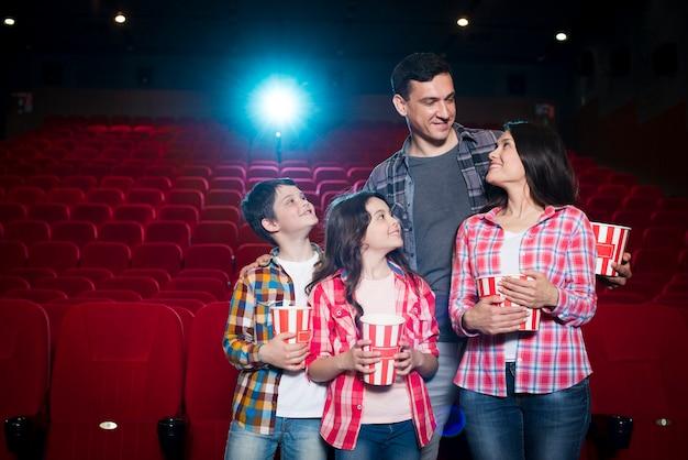 Famiglia felice che si siede nel cinema Foto Gratuite