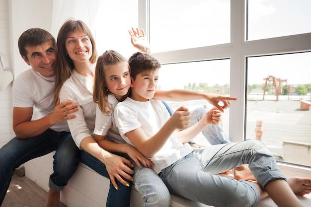 Famiglia felice che si siede sul davanzale della finestra e che gioca a casa Foto Gratuite