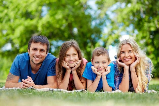 Famiglia felice che si trova in una fila Foto Gratuite