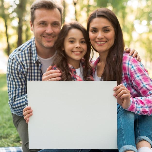 Famiglia felice che tiene cartello bianco in bianco nel parco Foto Gratuite