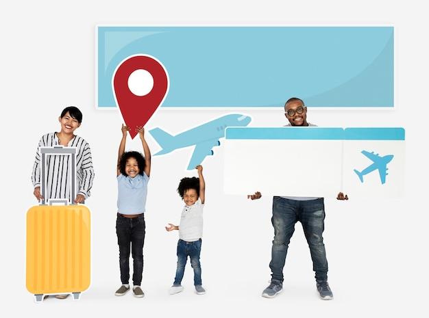 Famiglia felice che tiene icone e biglietto di viaggio Foto Premium