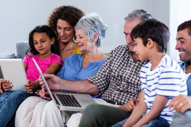 Famiglia felice che utilizza computer portatile e compressa digitale nel salone Foto Premium