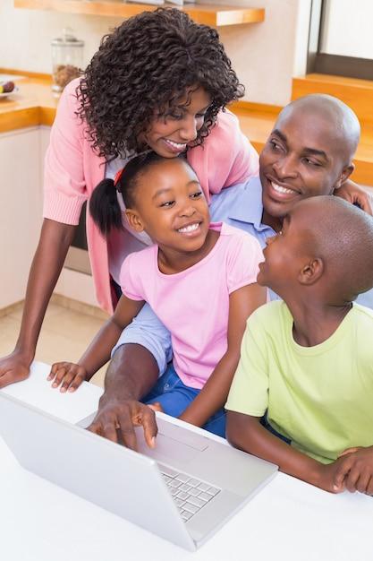 Famiglia felice che utilizza insieme il computer portatile a casa nella cucina Foto Premium
