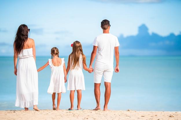 Famiglia felice con i bambini sulla spiaggia insieme Foto Premium