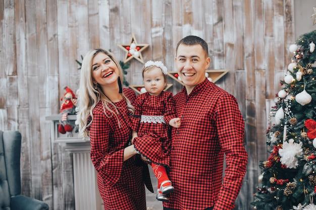 Famiglia felice con la sua piccola figlia insieme nella stanza decorata Foto Premium