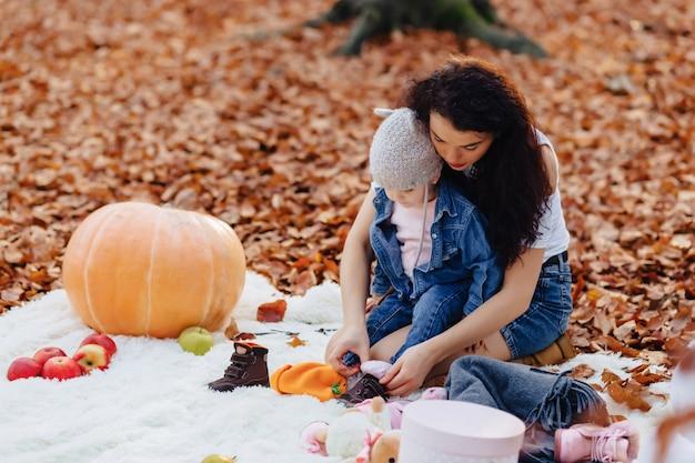 Famiglia felice con piccolo bambino sveglio nel parco sulla foglia gialla con grande zucca in autunno Foto Premium
