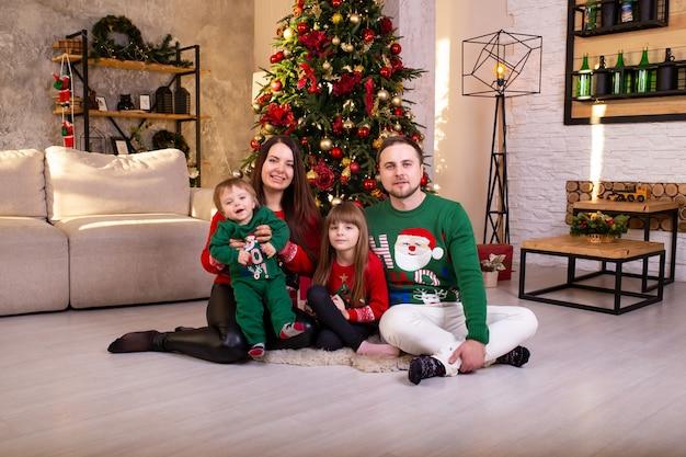 Famiglia felice divertendosi insieme a casa vicino all'albero di natale a Foto Premium