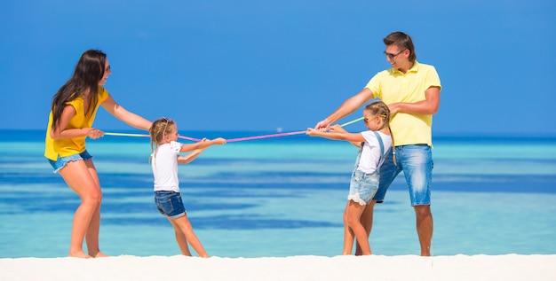 Famiglia felice divertirsi sulla spiaggia bianca Foto Premium