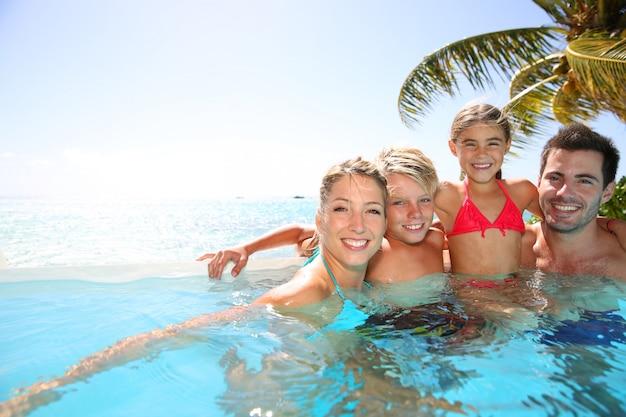 Famiglia felice godendo il tempo del bagno in piscina a sfioro Foto Premium