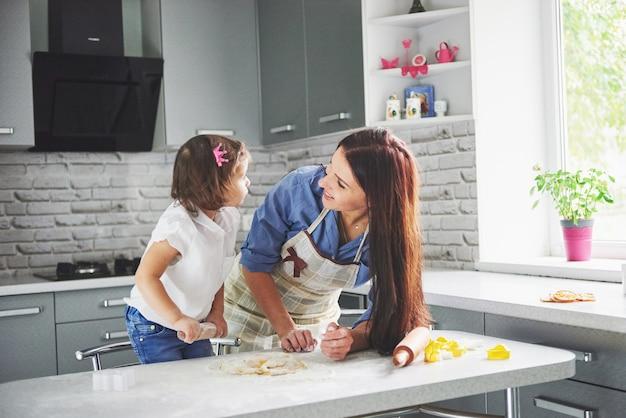 Famiglia felice in cucina. concetto di cibo per le vacanze. la madre e la figlia che preparano la pasta, cuociono i biscotti. famiglia felice nella produzione di biscotti a casa. cibo fatto in casa e piccolo aiuto Foto Gratuite