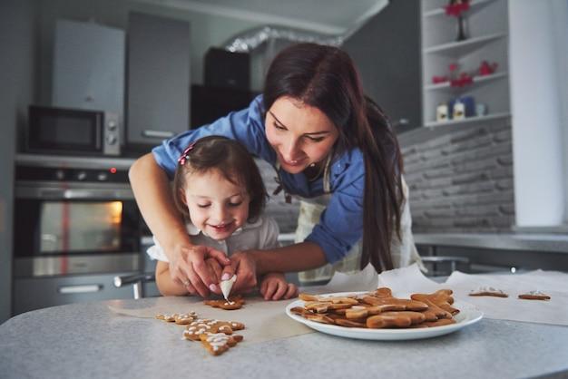 Famiglia felice in cucina. concetto di cibo per le vacanze. la madre e la figlia decorano i biscotti. famiglia felice nella produzione di pasticceria fatta in casa. cibo fatto in casa e piccolo aiuto Foto Gratuite