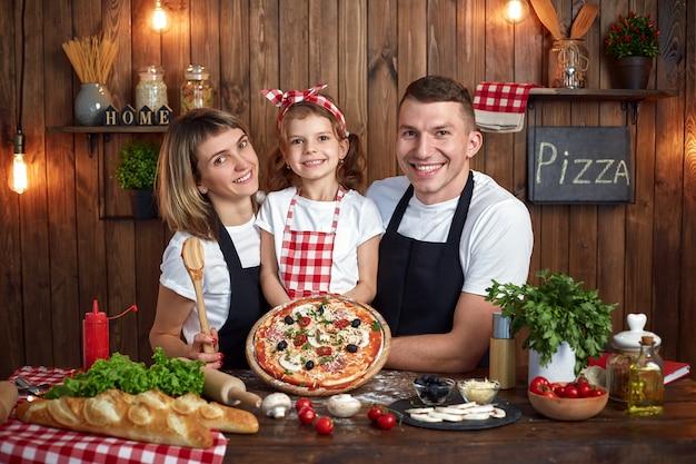 Famiglia felice in grembiuli che sorride e che tiene pizza cotta Foto Premium