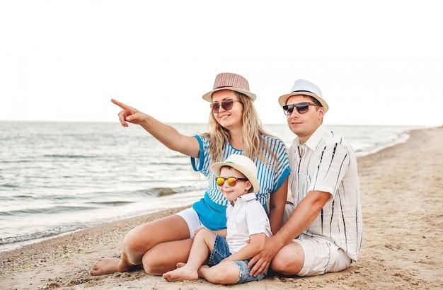 Famiglia felice in vacanza. sulla spiaggia si trovano mamma, papà e un figlio piccolo. famiglia in viaggio. baci, sorrisi Foto Premium
