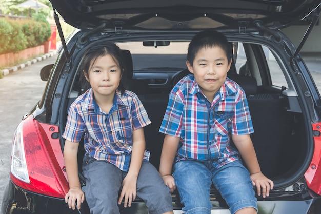 Famiglia felice in viaggio, seduti nel bagagliaio della macchina Foto Premium