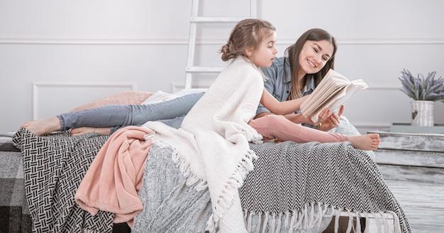Famiglia felice. madre e figlia che leggono un libro sul letto. Foto Gratuite