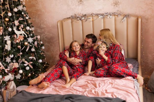 Famiglia felice madre padre e bambini sulla mattina di natale a letto in pigiama Foto Premium