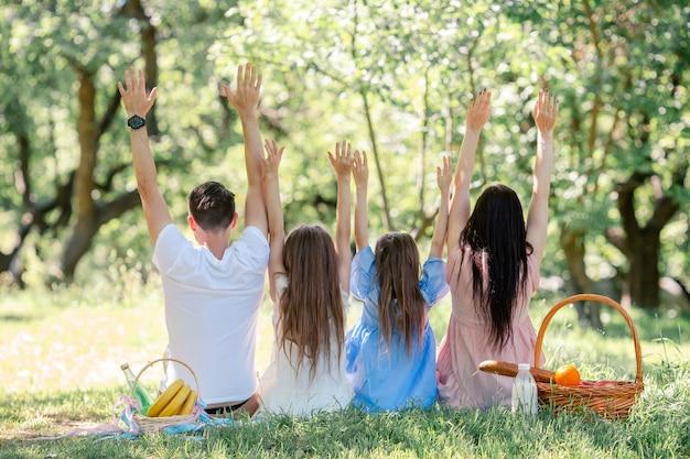 Famiglia felice su un pic-nic nel parco in una giornata di sole Foto Premium