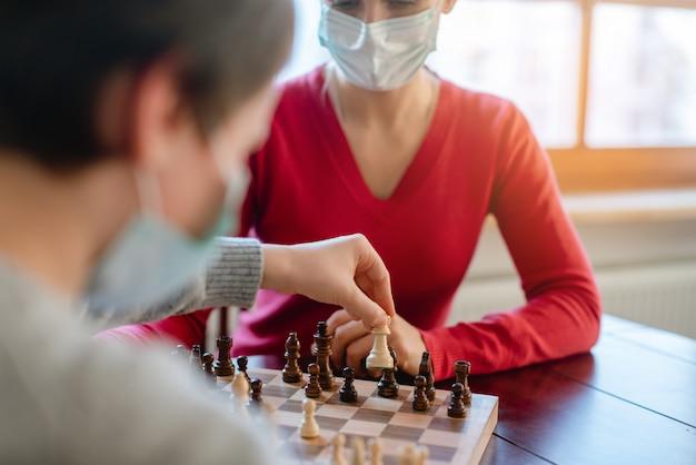 Famiglia giocando a giochi da tavolo durante il coprifuoco in movimento pezzi degli scacchi Foto Premium