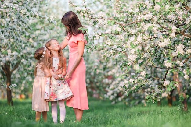 Famiglia in giardino fiorito di apple all'aperto Foto Premium