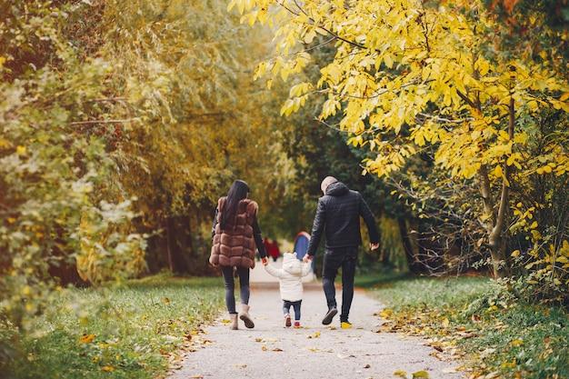 Famiglia in un parco in autunno Foto Gratuite