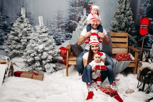 Famiglia insieme a natale nella foresta artificiale sotto nevicate Foto Premium