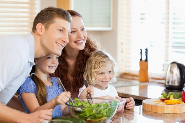 Famiglia insieme con insalata in cucina Foto Premium