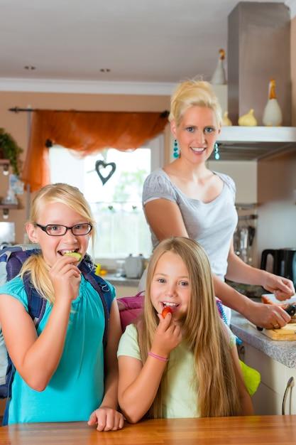 Famiglia, madre preparando la colazione per la scuola Foto Premium